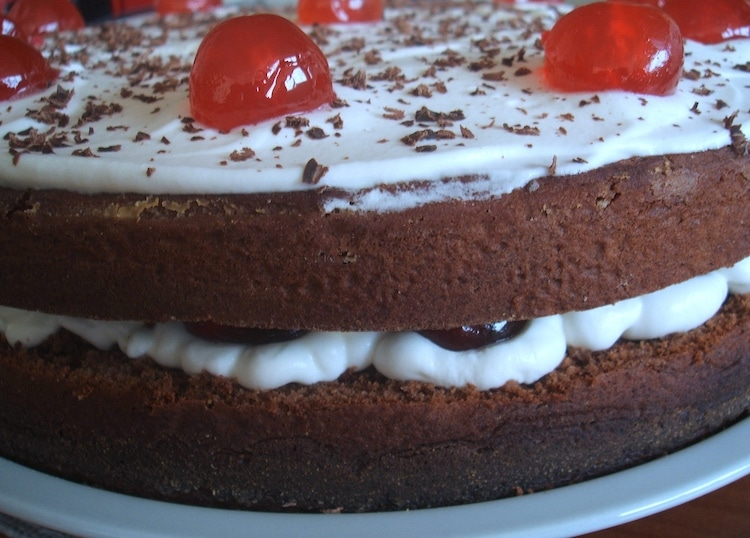 Bolo de chocolate com cerejas recheado com chantilly num prato