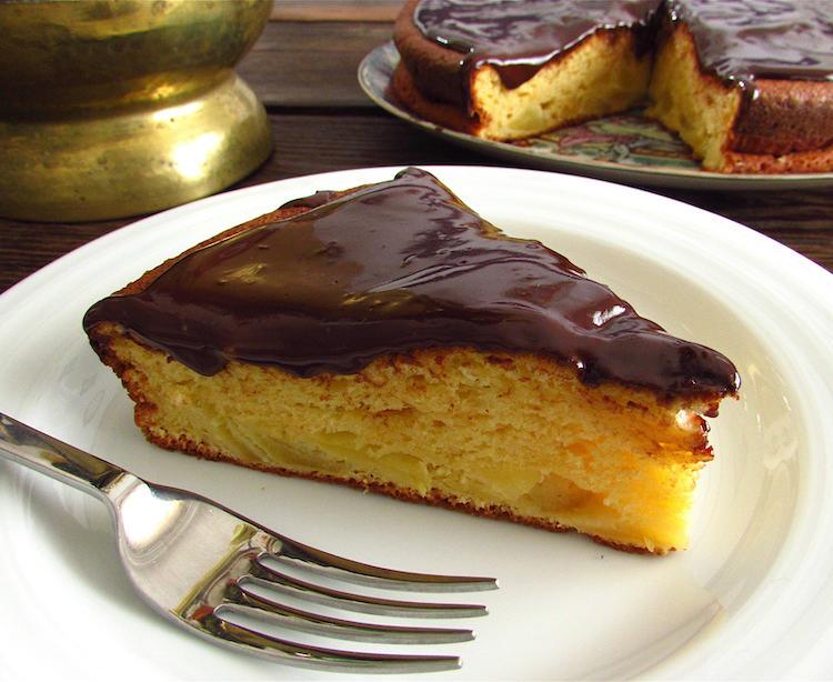 Fatia de bolo de maçã com cobertura de chocolate num prato