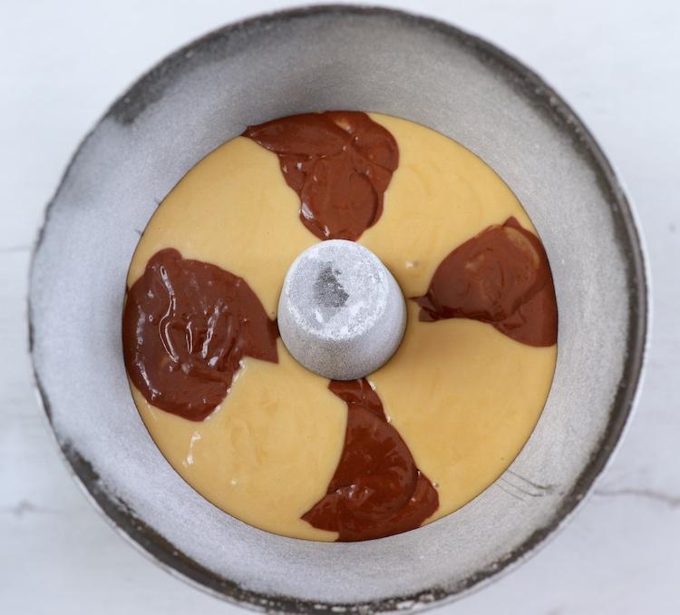 Massa de bolo mármore de chocolate numa forma de bolos redonda com furo no meio