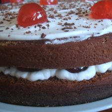 Chocolate cake garnished with cherries filled with chantilly on a plate