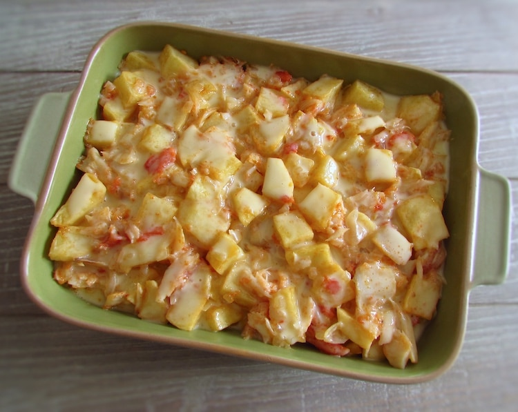 Cod and potatoes on a baking dish drizzled with a béchamel mixture