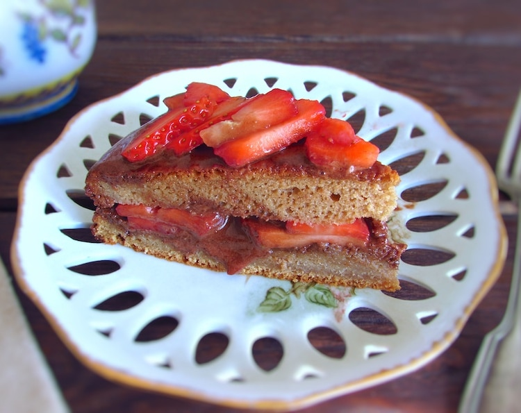 Slice of coffee cake with chocolate mousse and strawberries on a plate