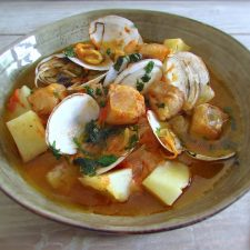 Monkfish stew with clams on a dish bowl