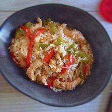 Bifes de peru com pimentos e arroz num prato fundo