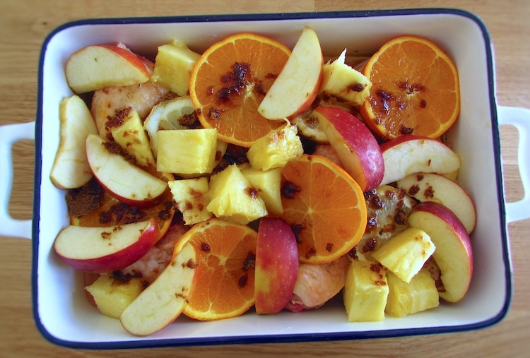 Chicken with apple, orange, pineapple and brown sugar on a baking dish