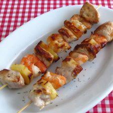 Espetadas de frango, camarão e ananás numa travessa