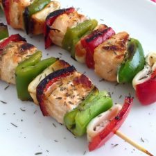 Salmon and squids kebabs on a plate