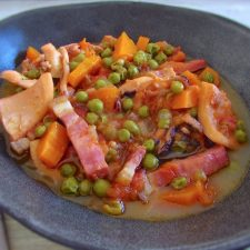 Cuttlefish with peas and carrots on a dish bowl