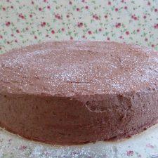 Bolo recheado com creme e coberto com chocolate num prato