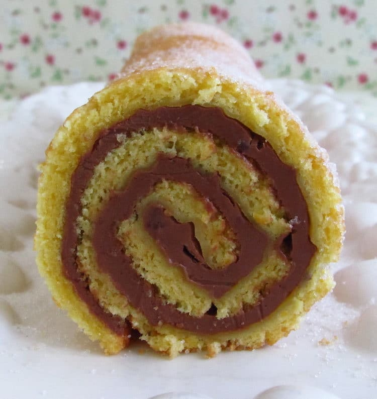 Orange roll cake filled with chocolate on a platter