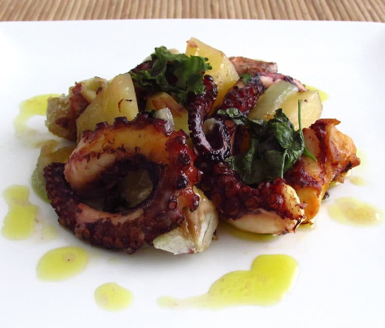 Octopus in the oven with chestnuts on a plate