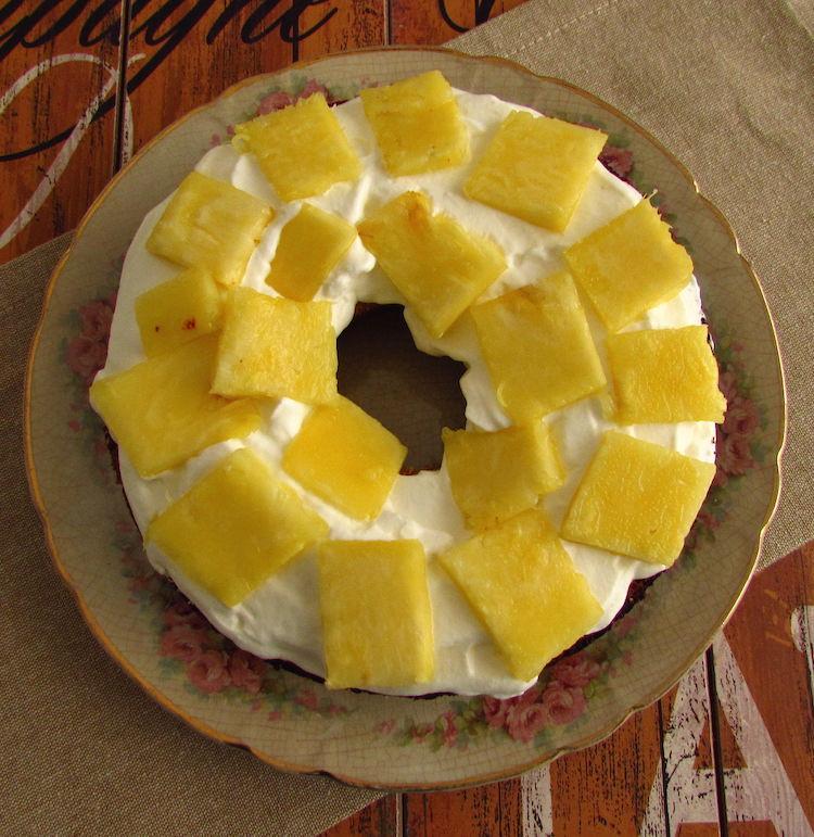 Pão de ló cortado ao meio num prato recheado com creme e pedaços de ananás