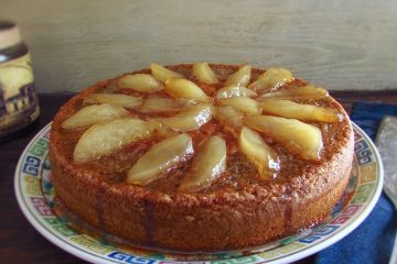 Rosemary cake topped with caramelized pear on a plate