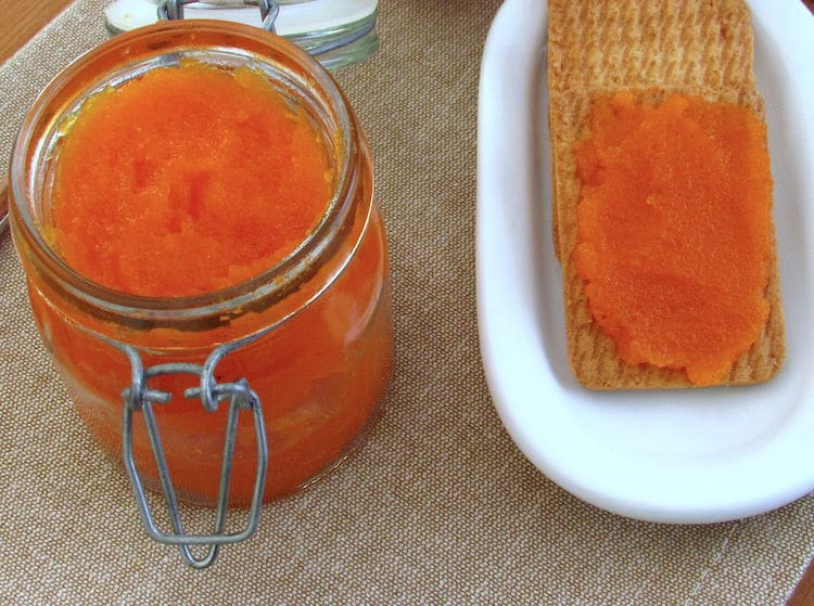 Carrot jam on glass jar with crackers