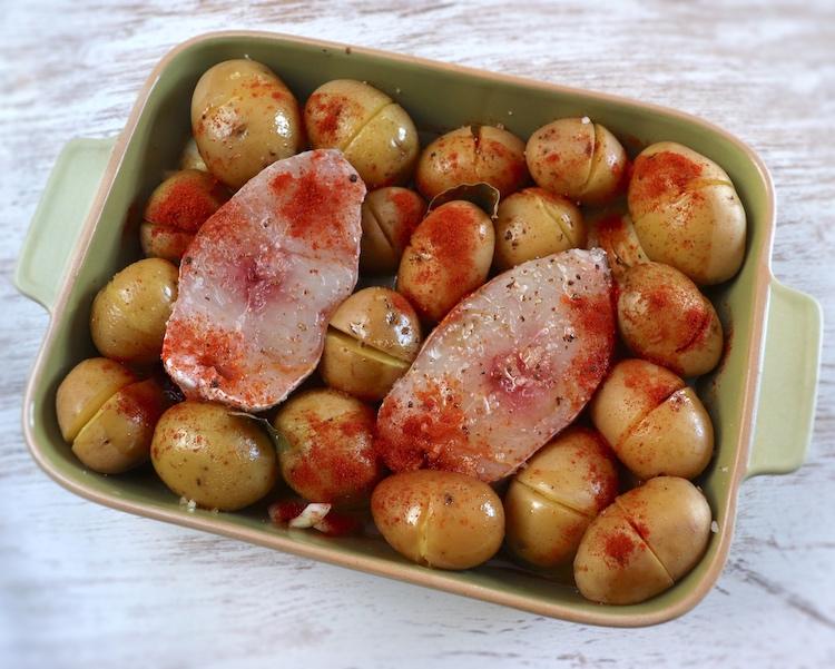 Garoupa e batatas com cebola, sal, azeite, vinho branco, pimenta, louro, alhos esmagados com casca e pimentão doce numa assadeira
