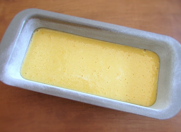 Orange and milk cake dough on a loaf tin