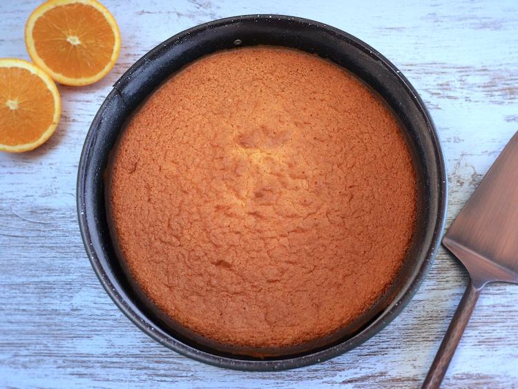 Orange sponge cake dough on a round cake pan