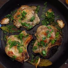 Fried pork chops with coriander on a frying pan