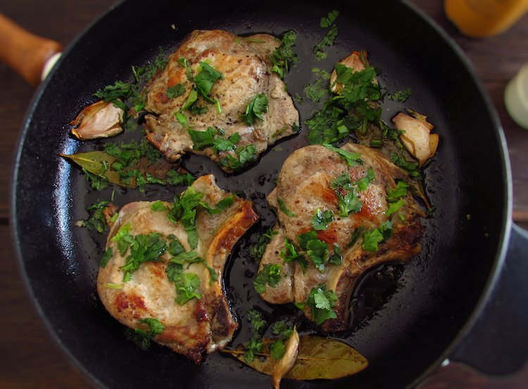 Fried chops with coriander on a frying pan