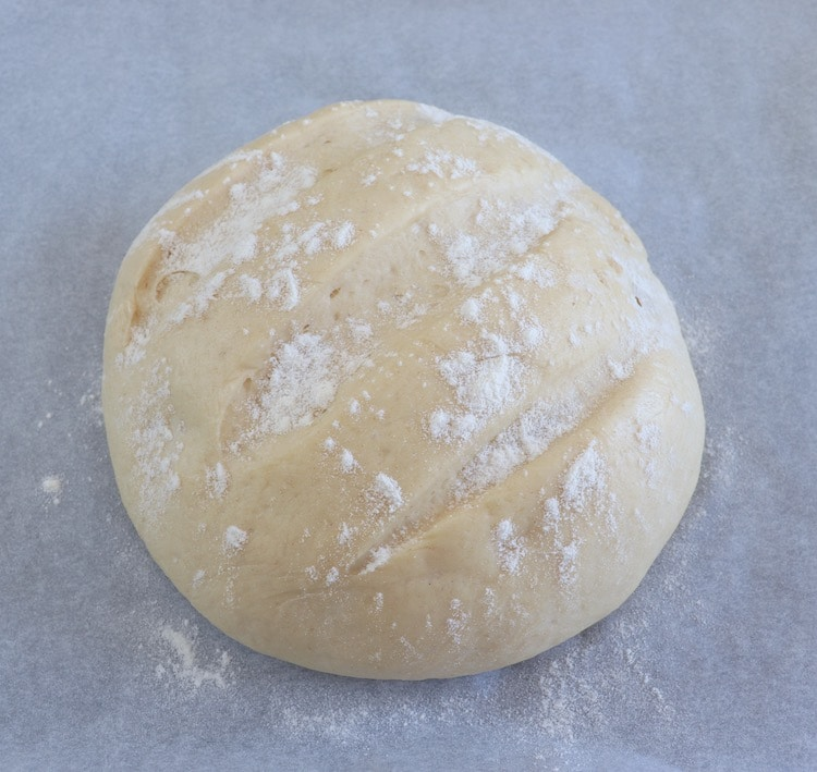 Bread dough sprinkled with flour on a baking tray lined with parchment paper