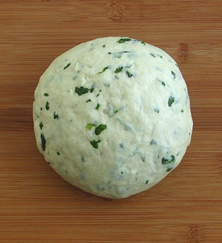 Coriander and garlic bread dough on a table