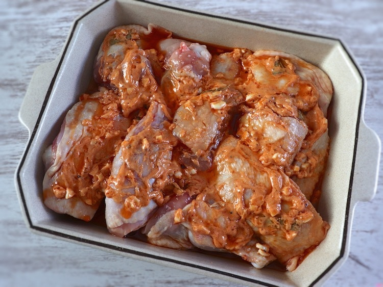 Chicken on a baking dish seasoned with salt, olive oil, chopped garlic, Dijon mustard, sweet red pepper paste, pepper and nutmeg