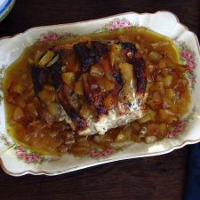 Pork loin in the oven with apple on a platter