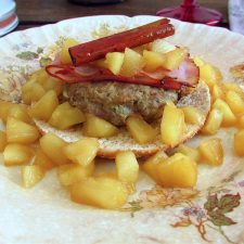 Burger with apple and bacon on a plate