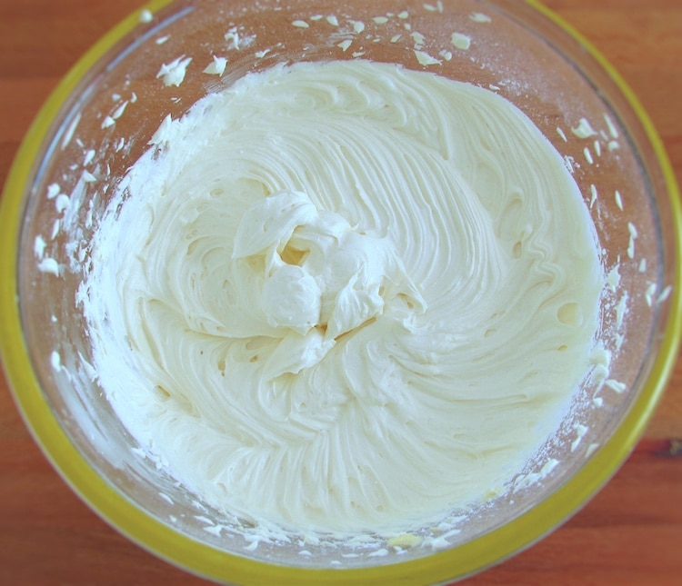 Mixture of butter, milk, vanilla extract and powdered sugar in a glass bowl
