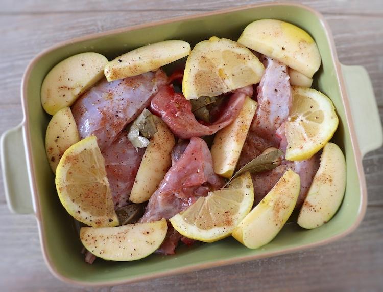 Pedaços de coelho temperados com sal, sumo de limão, pimenta, noz-moscada, louro, alhos descascados e o limão e as maçãs cortados aos quartos