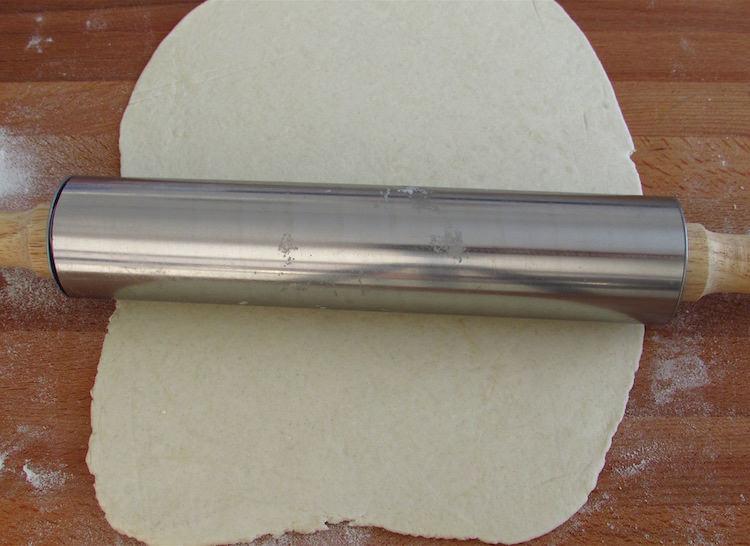 Massa folhada numa mesa polvilhada com farinha com um rolo da massa