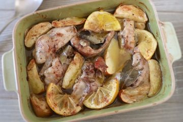 Rabbit in the oven with apple and lemon on a baking dish