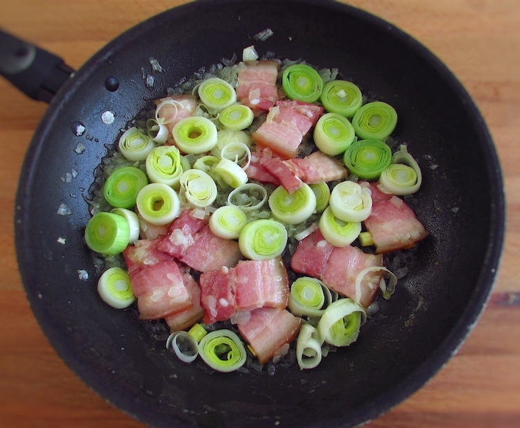 Olive oil, chopped onion, bacon and leek on a frying pan