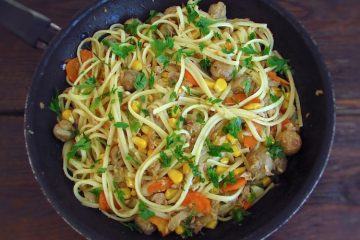 Spaghetti with tuna, corn and mushrooms on a frying pan