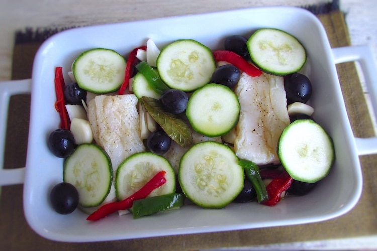 Cod loins, courgette, peppers and olives on a baking dish