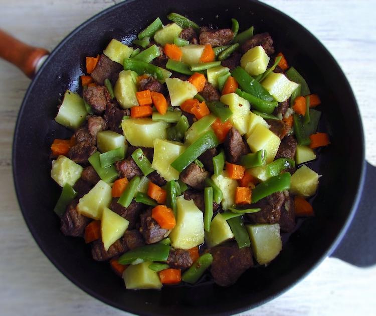 Vitela salteada com legumes numa frigideira