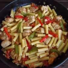 Pasta with pork and peppers on a frying pan