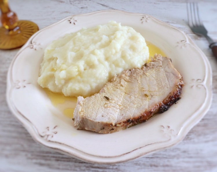 Slice of pork loin with spices with mushed potato on a plate