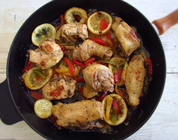 Fried chicken with peppers and lemon on a frying pan
