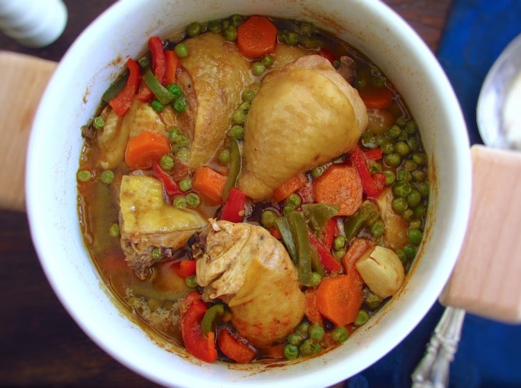 Chicken stew with peas, carrot and peppers in a pot