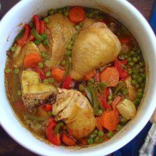 Frango guisado com ervilhas, cenoura e pimentos num tacho