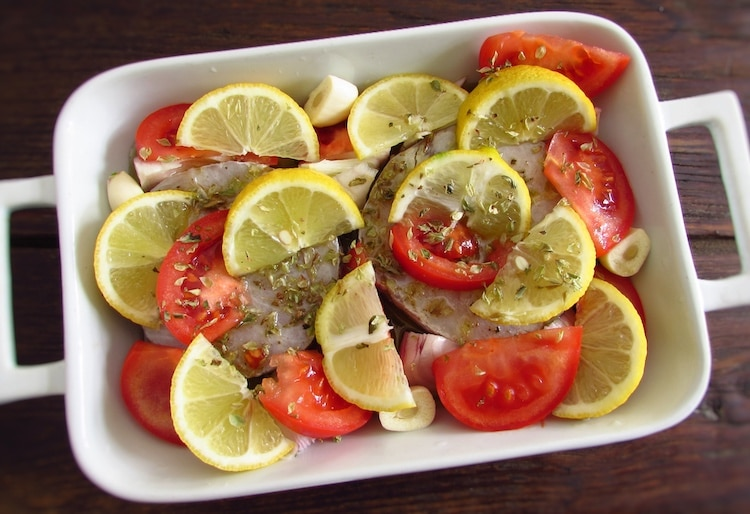 Hake with onion, tomato and lemon seasoned with salt, oregano, pepper, lemon juice, peeled garlic and olive oil on a baking dish