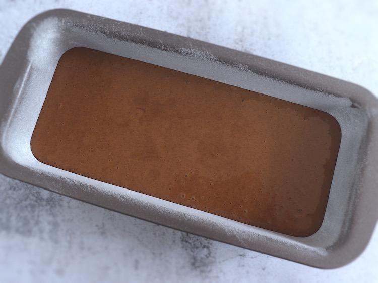 Massa de açúcar mascavado, azeite e canela numa forma de bolos rectangular