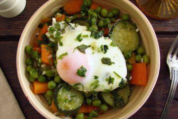 Ervilhas com cenoura, curgete e ovos escalfados num prato
