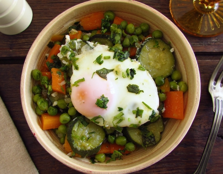 Peas with carrot, courgette and poached eggs on a dish