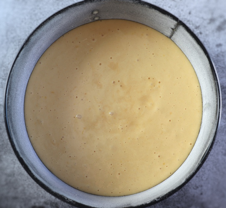 Soaked pineapple cake dough on a round cake pan