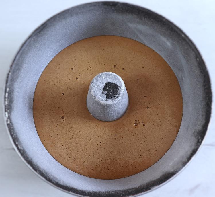 Massa de bolo de laranja e açúcar mascavado numa forma de bolos redonda com furo no meio