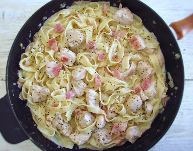 Fried chicken breast with bacon and tagliatelle on a frying pan
