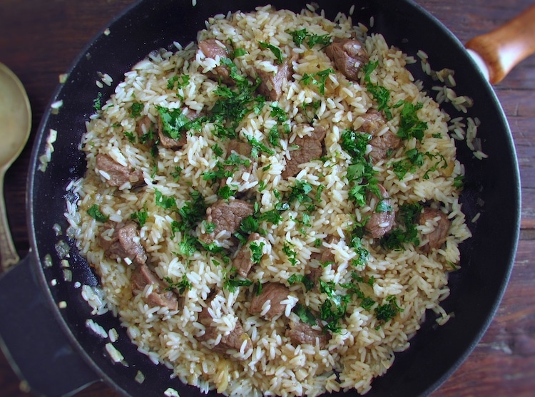 Fried veal with rice on a frying pan