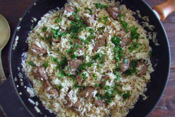 Vitela frita com arroz numa frigideira
